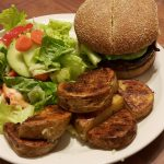 Portabello mushroom burger with roasted potatoes and a side salad